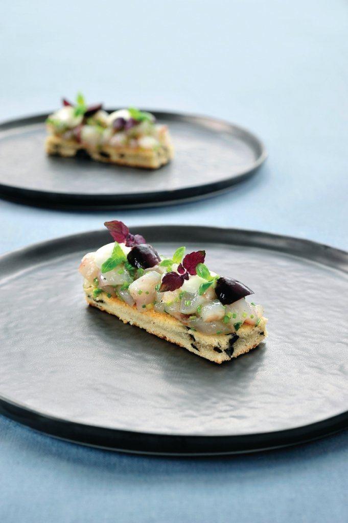 Tartaar van zeebaars op biscuit geserveerd